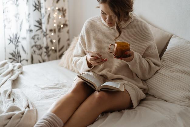 熱いお茶を飲み、電話を使用している女性。快適なライフスタイル。