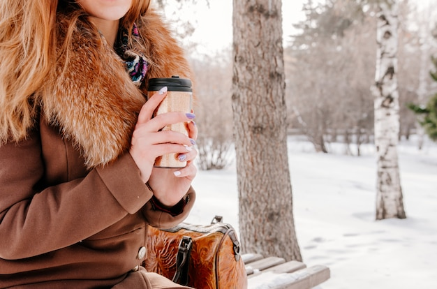 Woman drinking hot tea from thermo cup