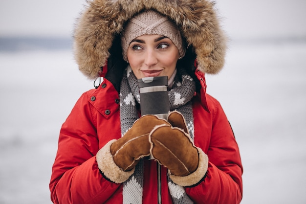 Woman drinking hot tea in winter outside