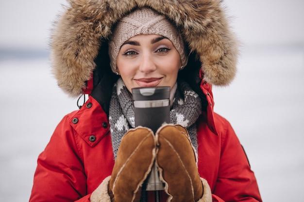 Woman drinking hot tea in winter outside
