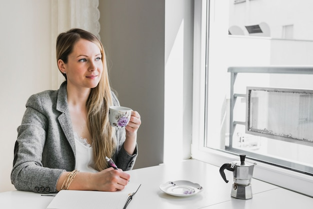 Woman drinking and making notes Free Photo