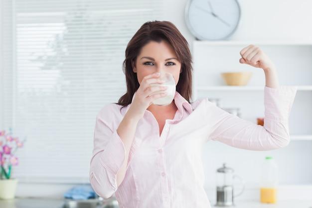 Женщина выпивает молоко и сгибает мышцы