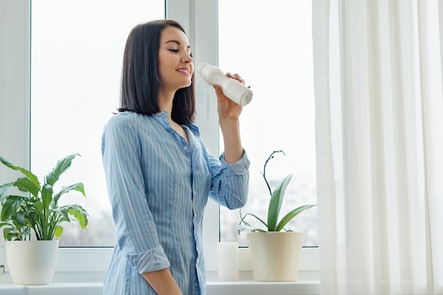 Woman drinking milk drink yogurt from bottle