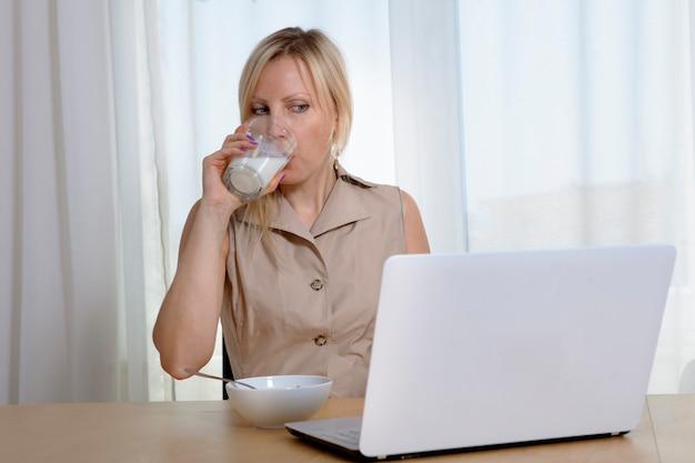 Женщина пьет молоко из стакана, завтракает и работает в интернете.
