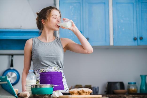 Woman drinking milk in kitchen
