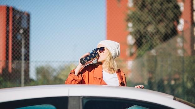 Женщина, пить возле автомобиля