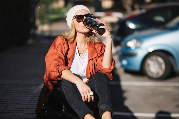 駐車場で飲む女性