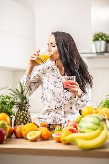 果物でいっぱいのキッチンでカップからオレンジジュースを飲む女性。