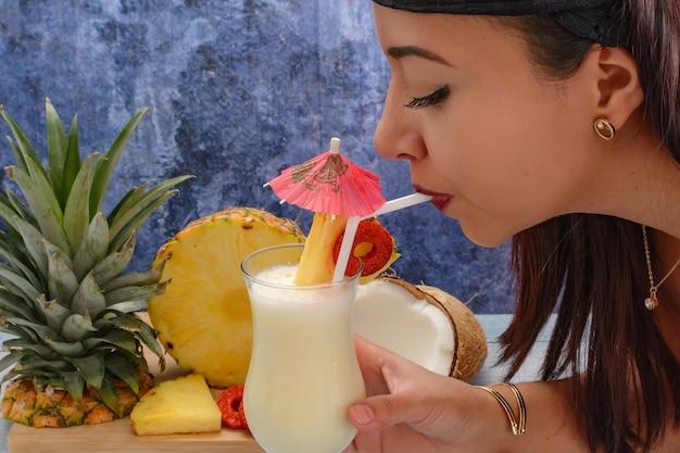 Женщина пьет пина колада со свежими фруктами на деревянной разделочной доске на синем текстурированном фоне