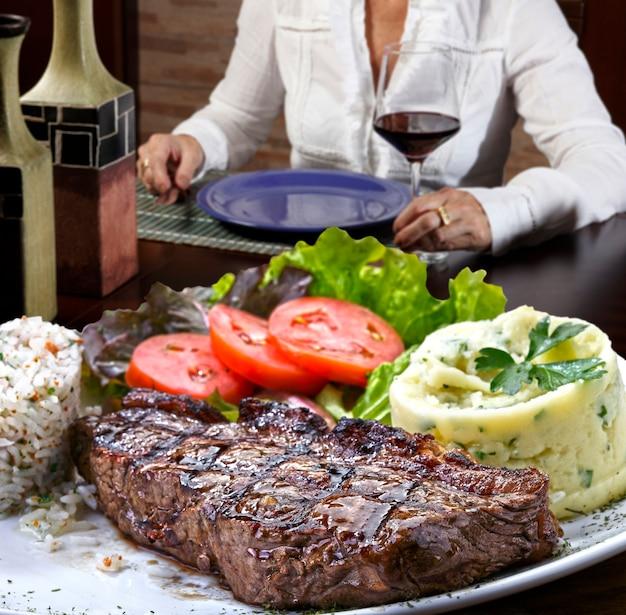 Женщина пьет красное вино и ест стейк на гриле с картофельным пюре и салатом