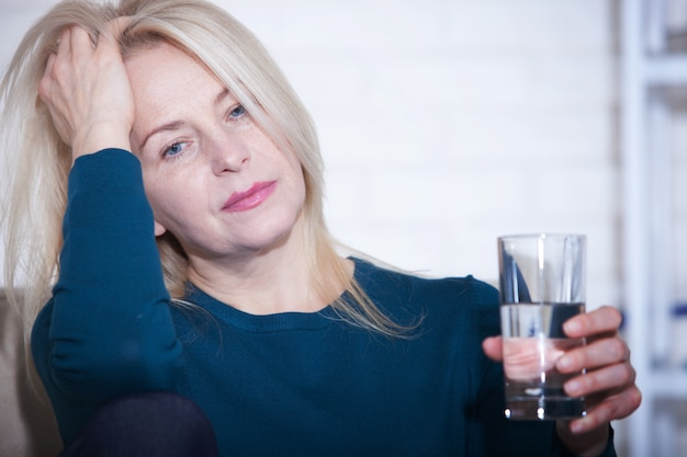 Woman drinking sitting at home in a depressed state.