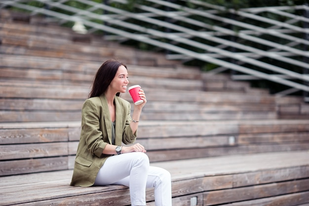 Woman drinking tasty coffee outdoors in the park