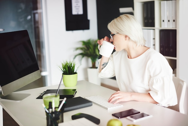 お茶を飲み、ホームオフィスでタイピングする女性