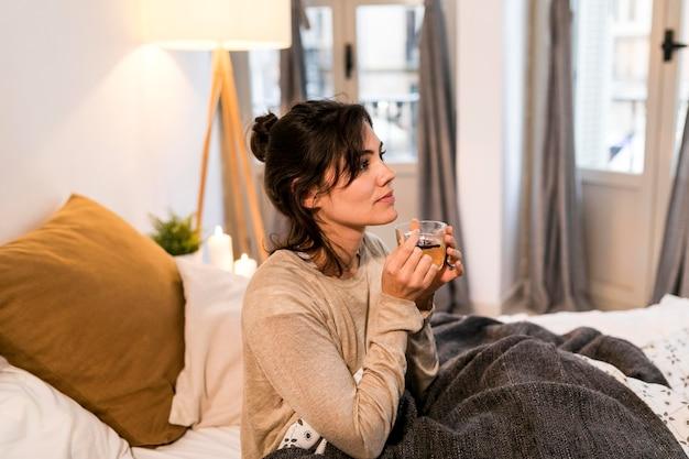Donna che beve il tè a letto