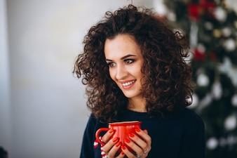 Woman drinking tea by Christmas tree