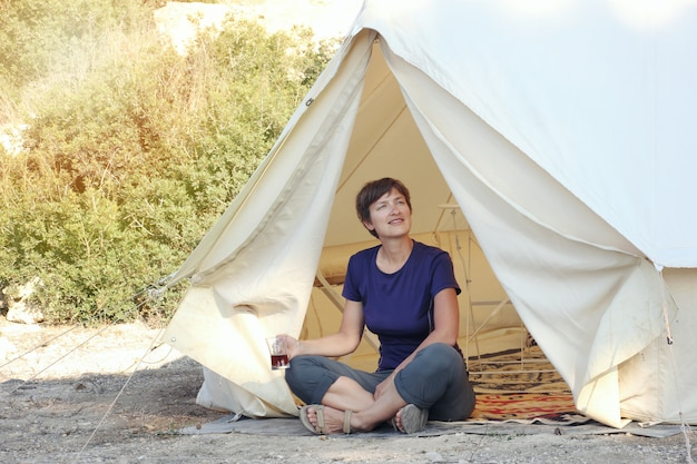 Woman drinking tea near big glamping tent with cozy interior