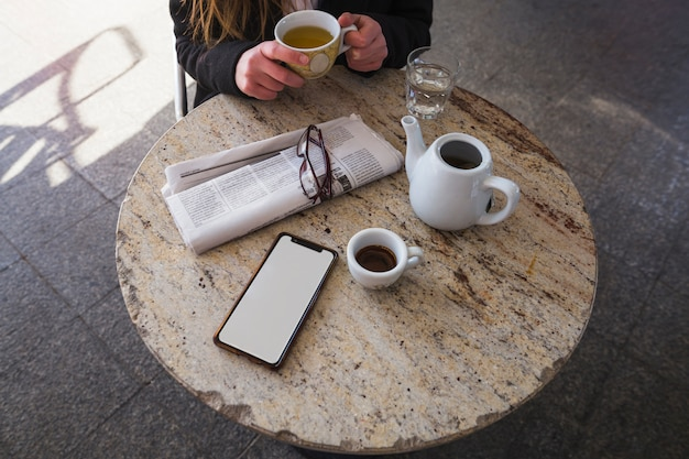 Woman drinking tea at table with newspaper and smartphone