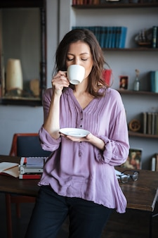 自宅のテーブルにもたれながらお茶を飲む女性