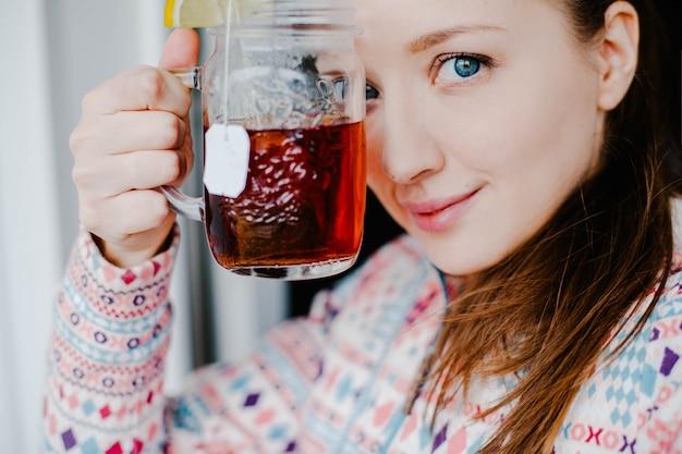 Woman drinking tea with lemon
