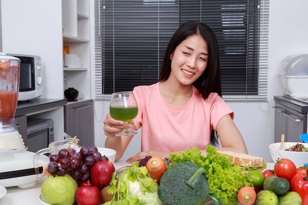 Woman drinking vegetable juice in kitchen