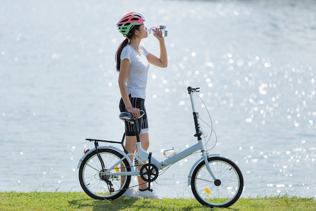 Woman drinking water after exercise bike.