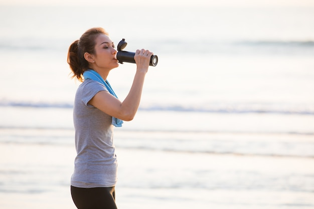 Woman drinking water after exercise.