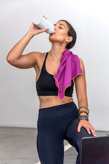 Woman drinking water after practicing an online yoga session at home
