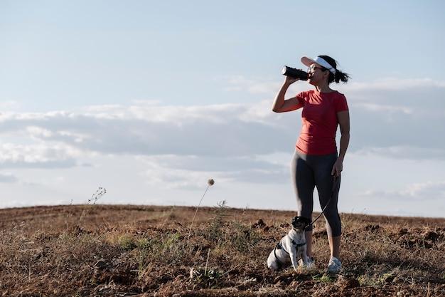 彼女の犬と一緒に走った後水を飲む女性