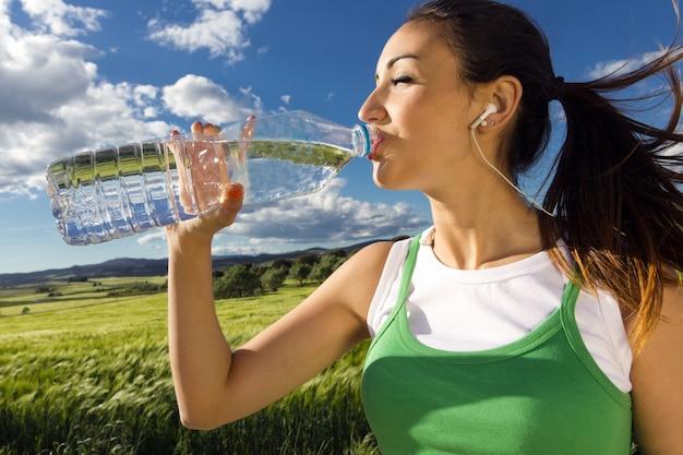 Женщина питьевой воды после занятий спортом