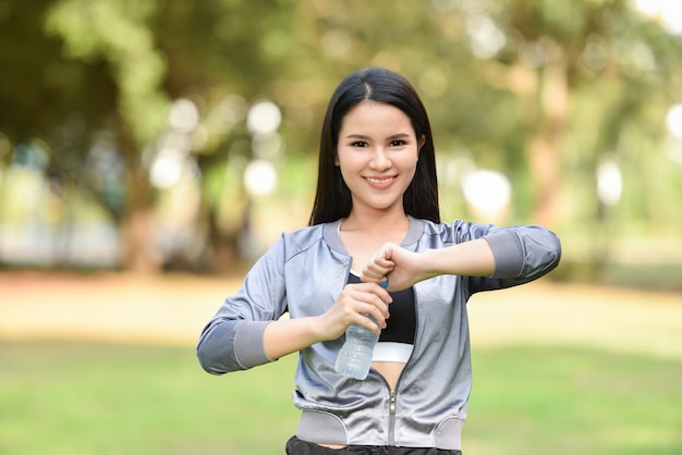 Woman drinking water bottle health concept / smiling young girl relax exercise and hold water bottle