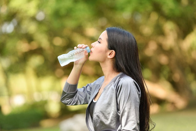 Woman drinking water bottle health concept smiling young girl relax