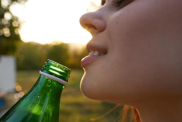 さわやかな飲み物の夏のガラス瓶から水を飲む女性