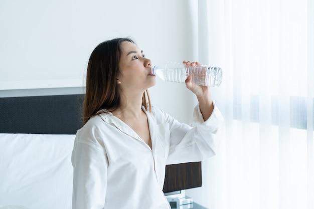 Женщина пьет воду из прозрачной пластиковой бутылки
