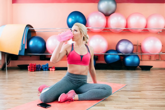 Woman drinking water from bottle after training