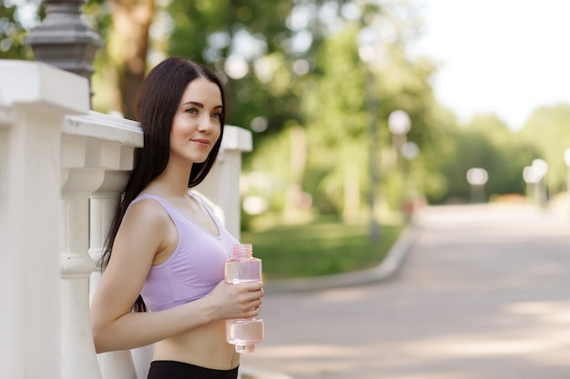 Woman drinking water from bottle after workout at park to stay hydrated.