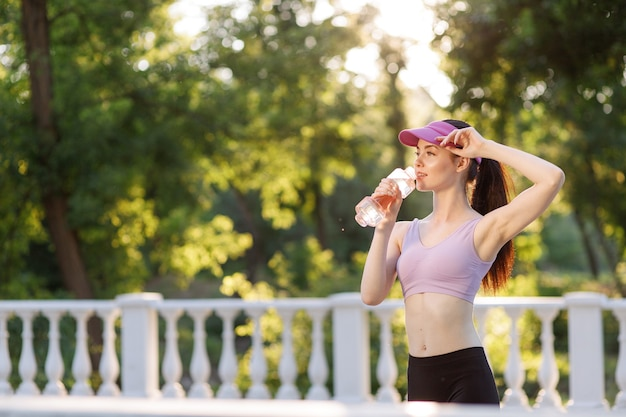 Woman drinking water from bottle after workout at park to stay hydrated