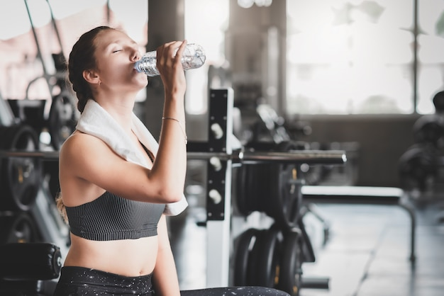 Woman drinking water from bottle after workout
