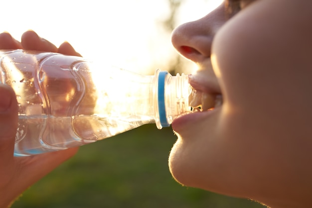 Woman drinking water from a bottle face closeup summer