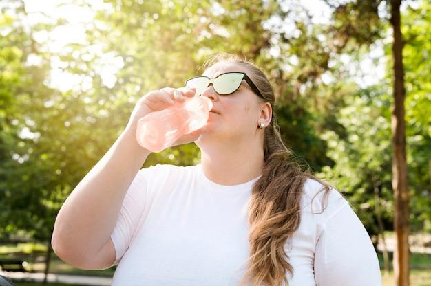 Женщина пьет воду в парке
