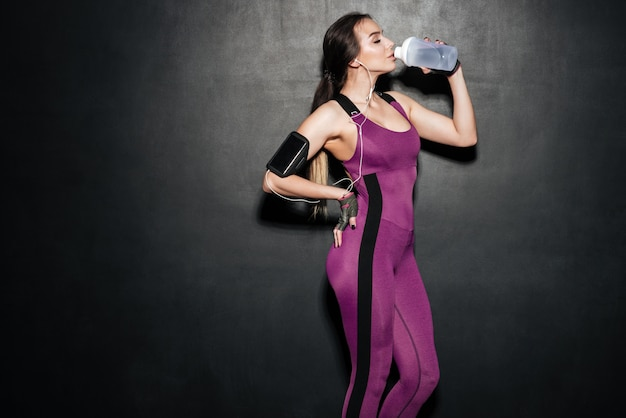 Woman drinking water and listening music isolated