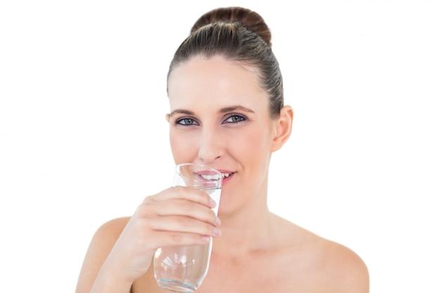 Woman drinking water looking at camera