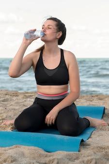 Женщина пьет воду на коврике для йоги
