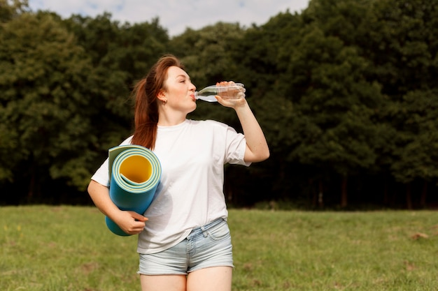 Woman drinking water outdoors