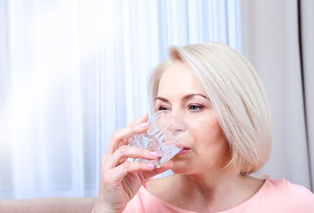 Женщина пьет воду, сидя на диване у себя дома