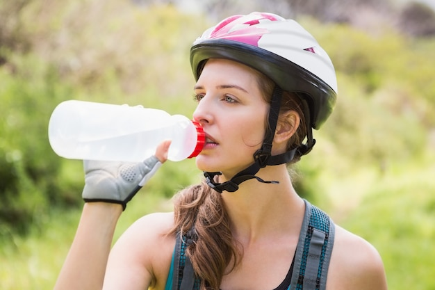 Woman drinking water and wearing helmet