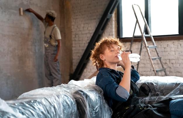 Женщина пьет воду, пока мужчина красит стену своего нового дома