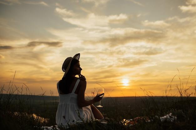 旅行、休日、休暇でゴージャスな夕日を見ながら白ワイングラスを飲む女性。