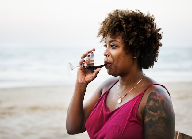 Woman drinking wine on the beach
