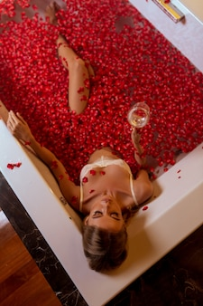Woman drinking wine while relaxing in luxury spa bath, top view from above. spending romantic evening or night in bathroom.