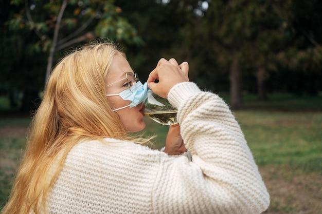 얼굴 마스크를 착용하는 동안 와인을 마시는 여자